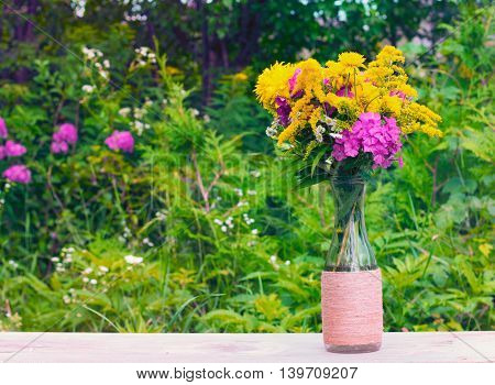 a bouquet of flowers of goldenrod Phlox and chrysanthemums in a glass bottle on a natural background. tinted photo