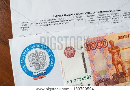VELIKY NOVGOROD RUSSIA-JULY 24 2016. Tax payment notice letter with logo of Federal Tax Service of the Russian Federation and five thousand ruble banknote above. The concept of tax on personal income