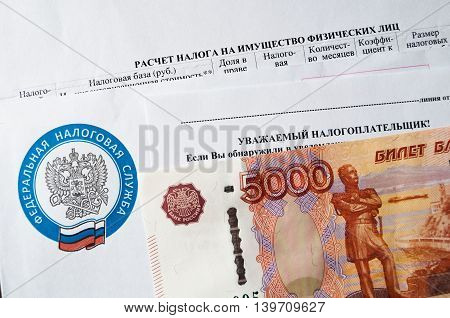 VELIKY NOVGOROD RUSSIA-JULY 242016. Tax payment notice letter with logo of Federal Tax Service of the Russian Federation and five thousand ruble banknote above. The concept of tax on personal income
