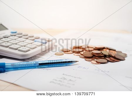 Bill with calculator and coins and pen on white background vintage style