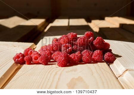 Heap of fresh raspberry on wooden boards