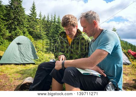 Evening in the camp in the Carpathian Mountains. Two hikers discussing the route looking at the map