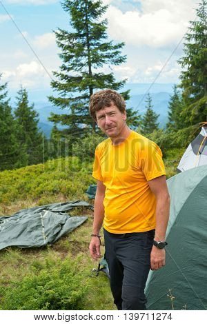 The red-haired hiker near the tent smiling and looking at the camera. Hiking in the Carpathian mountains.