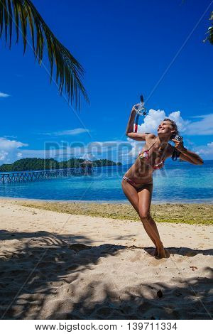 Photo young girl playing on beach snorkeling equipment. Smiling woman spending chill time outdoor summer Bali island. Horizontal picture