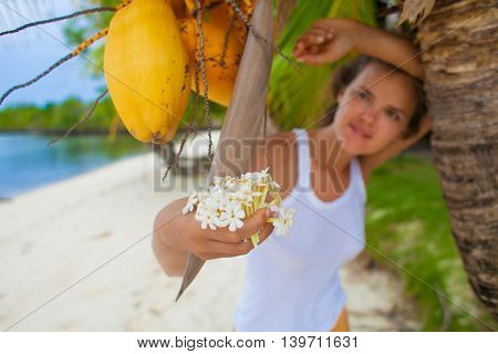 Photo young girl relaxing on beach with flowers. Smiling woman spending chill time outdoor summer Bali island. Horizontal picture Closeup