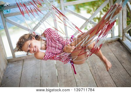 Photo young sexy girl relaxing on beach Bungalow in hammock. Smiling woman spending chill time outdoor summer. Caribbean Ocean Vacations. Horizontal, blurred background