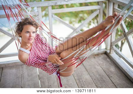 Photo young pretty girl relaxing on beach Bungalow in hammock. Smiling woman spending chill time outdoor summer. Caribbean Ocean Vacations. Horizontal, blurred background