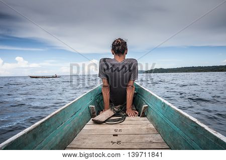 Photo of Man Sitting Natural Wood Long Tail Boat Caribbean Ocean. Clear water and blue sky with clouds. Horizontal