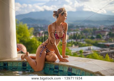 Photo Young Sexy girl Relaxing on Swimming Pool Terrace with Beautiful View. Smiling Woman Spending Chill Time Outdoor Summer. Caribbean Ocean Vacations. Horizontal, blurred background