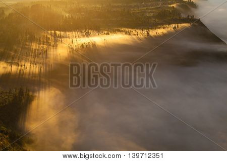 Sunrise Mountains.Asia Nature Morning Volcano Viewpoint.Mountain Trekking, View Landscape Valley Bali Village. Nobody photo. Horizontal picture. The first rays of the rising sun.White Fog Jungle Forest