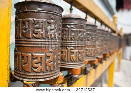 Tibetan prayer wheels or prayers rolls of the faithful Buddhists. Horizontal. Closeup photo