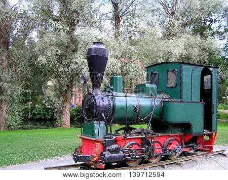 Old green locomotive standing on the short railway track.