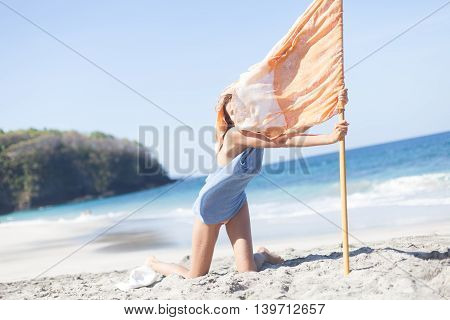 Photo young girl relaxing on beach holding flag. Smiling woman spending chill time outdoor summer. Horizontal picture