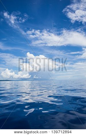 Photo of Blue Sea and Tropical Sky Clouds. Seascape. Sun over Water, Sunset. Horizontal. Nobody Picture. Ocean Background