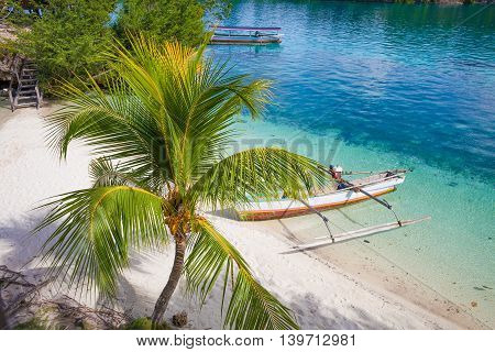 Photo Natural Wood Long Tail Boat Parked Caribbean Ocean Beach Island. Clear blue water. Horizontal