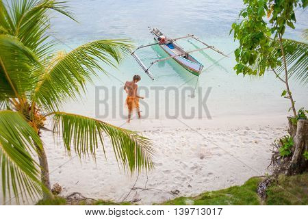 Photo Natural Wood Long Tail Boat Parked Caribbean Ocean Beach Island. Clear Blue Water Green Palm and Young Girl Background. Horizontal