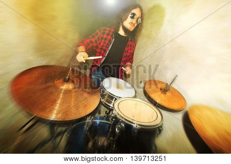 Drums conceptual image. Rock drummer holding drumsticks and playing on drums. Retro vintage grunge picture.