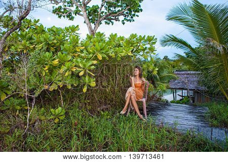 Photo Young Pretty Girl Enjoying Exotic Fruits in Jungle House Sunset. Smiling Woman Spending Chill Time Outdoor Summer. Horizontal Picture, Bali Island
