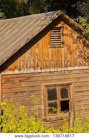 Old abandoned wooden house with weathered broken window on a calm summer day