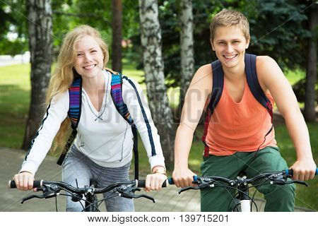 Young couple riding bicycle outdoors at summer