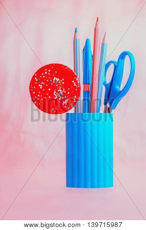 Blue pencil-box with pencils scissors and red round candy on a pink background. Selective focus.