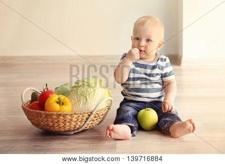 Cute baby and fresh vegetables in wicker basket on wooden floor
