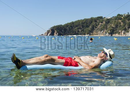 Retired man sleeping with inflatable bed floating in the sea