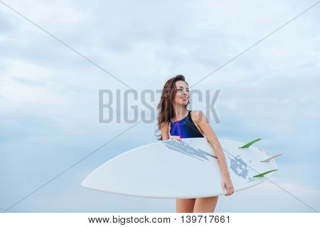 Young beautiful woman in swimsuit holding surfboard the beach