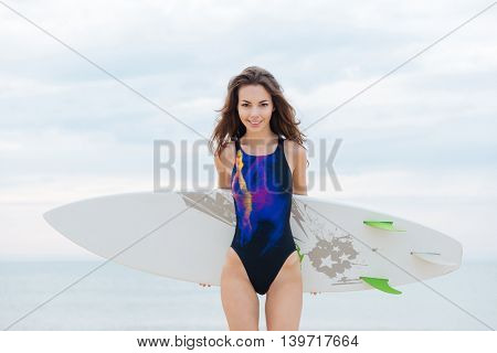 young surfer girl standing with surfboard on the beach