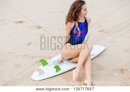 Beautiful young surfer girl sitting on surf board