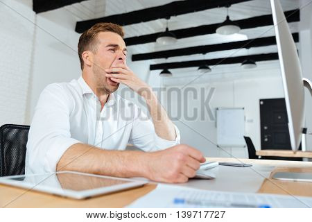 Sleepy tired young businessman working and yawning in office