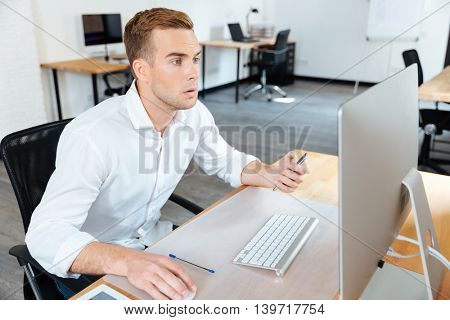 Pensive young businessman sitting in office and working with computer