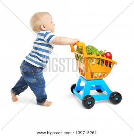 Cute baby with shopping trolley full of vegetables on white background