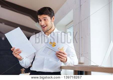 Happy young smiling businessman looking at documents while standing at the office
