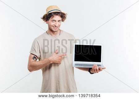 Smiling attractive young man holding blank screen laptop and pointing at it over white background