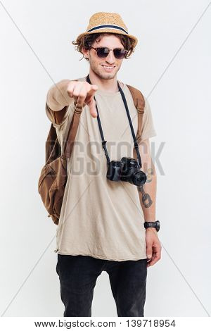 Young smiling man pointing finger at camera over white background