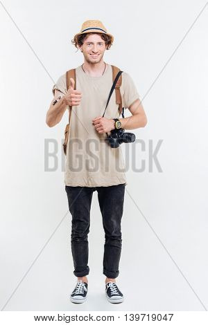 Full length portrait of handsome male tourist looking at camera and showing thumbs up gesture isolated on a white background