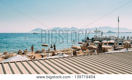 Beach Sun Loungers. Chaise-longues On The Beach. Sunbed And Umbrella On Beach In Cannes France.