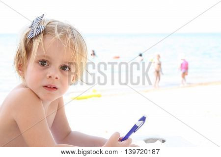 Portrait of baby girl drawing on the beach