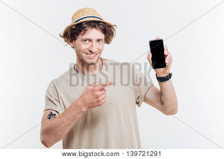 Portrait of a happy man pointing finger at smartphone with blank screen isolated on a white background