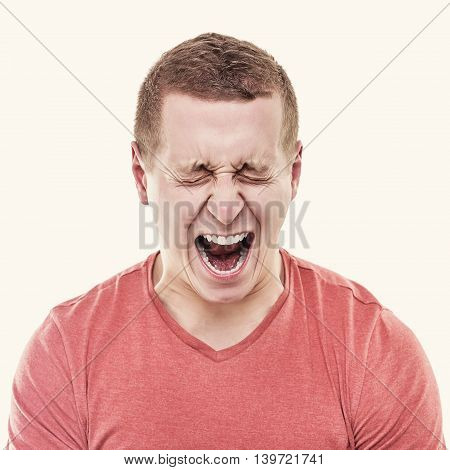 Angry man on a white background screaming. Toned photo.