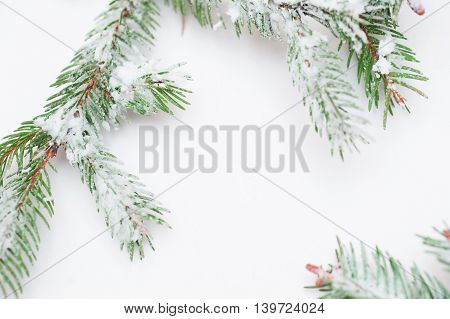 snow-covered fir branches and Christmas decorations with space for text.