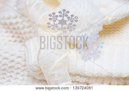 Warm woolen knitted hat and scarf with big white snowflakes.