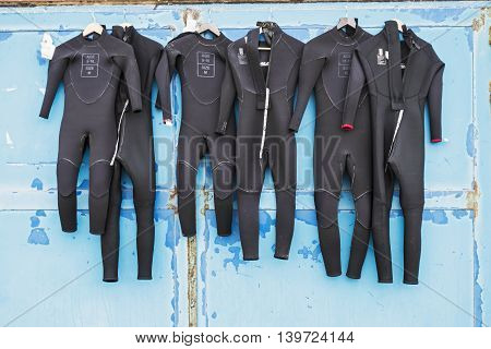 Wetsuits in children's sizes dry in the sun on a door of blue which is rusting in places due to salt corrosion of sea air.