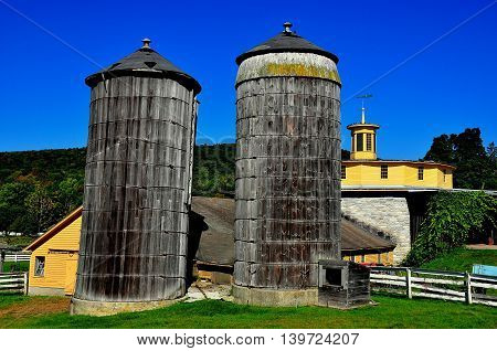 Hancock Massachusetts - September 17 2014: Two large wooden silos behind the 1826 round stone barn at the Hancock Shaker Village *