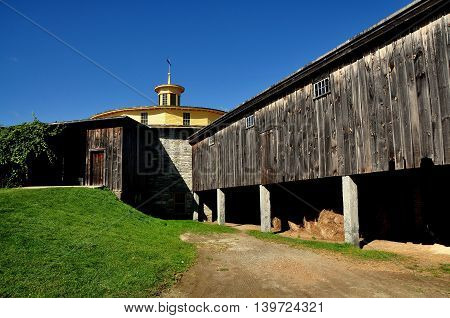 Hancock Massachusetts - September 17 2014: Wooden entrance and side wing used for storing hay at the 1826 round stone barn at the Hancock Shaker Village