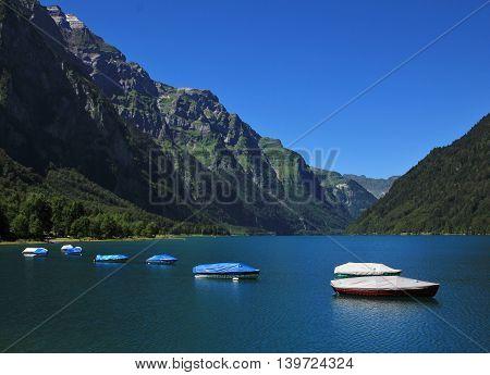 Boats on lake Klontal. Mt Glarnisch. Summer scene in the Swiss Alps
