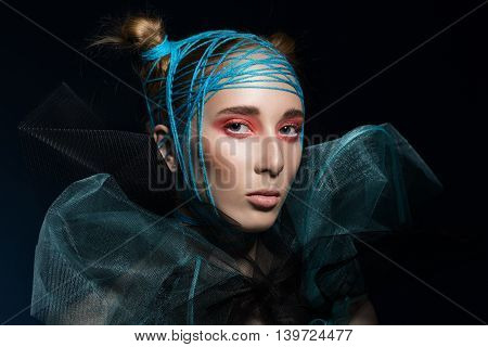 Beauty fashion model girl wearing Knitting thread on head.bright pink makeup and extravagant hairstyle. Blonde hair with two hair bundle in Knitting thread. Black background.