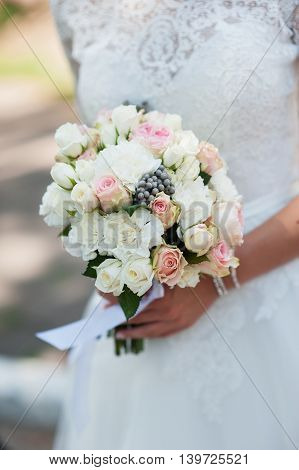Wedding Flowers Roses Bouquet in Bride Hands with White Dress on Background.