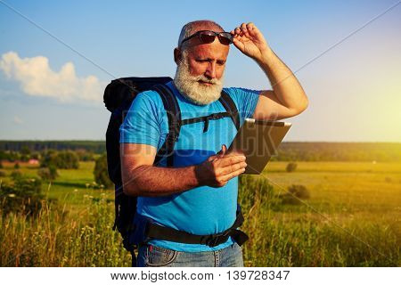 Handsome man with white beard in sunglasses with rucksack is using data tablet against sunlit field background